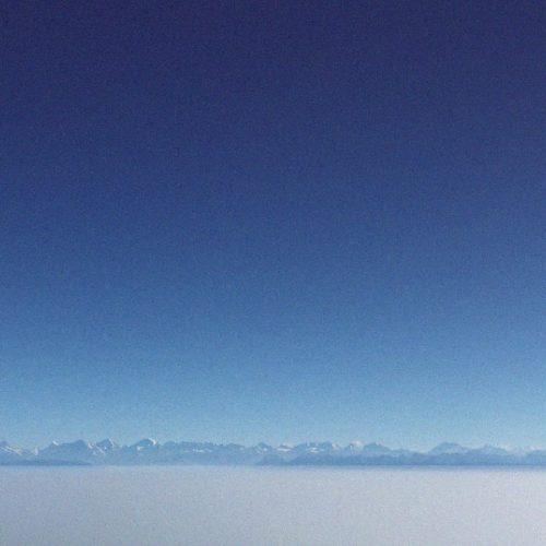 Berge im Nebel unter klarem blauem Himmel